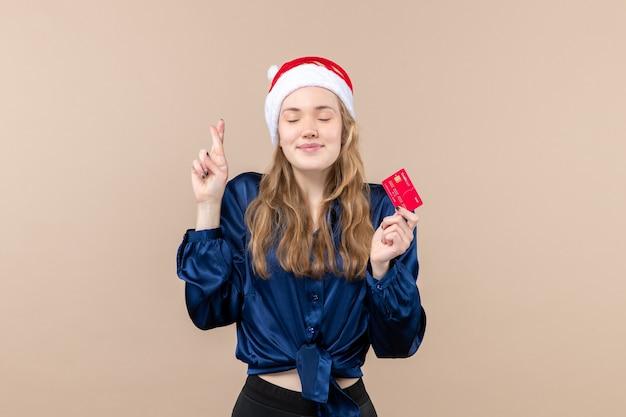 Vista frontal joven mujer sosteniendo tarjeta bancaria roja sobre fondo rosa vacaciones navidad dinero foto año nuevo emoción