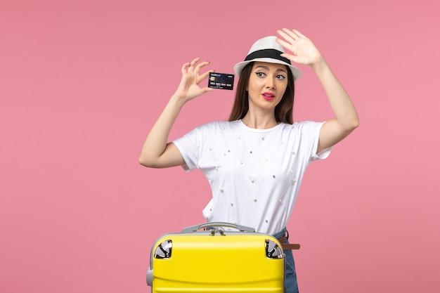 Vista frontal joven mujer sosteniendo tarjeta bancaria en viaje de verano de viaje de pared rosa