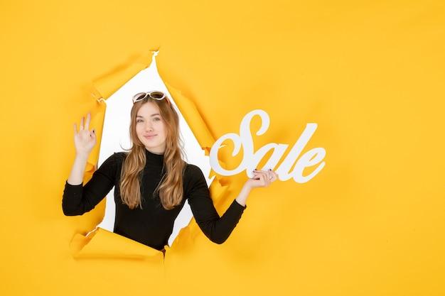 Vista frontal joven mujer sosteniendo venta escribiendo a través del agujero de papel rasgado en la pared