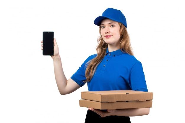 Una vista frontal joven mujer trabajadora de mensajería del servicio de entrega de alimentos con cajas de smartphone y pizza en blanco