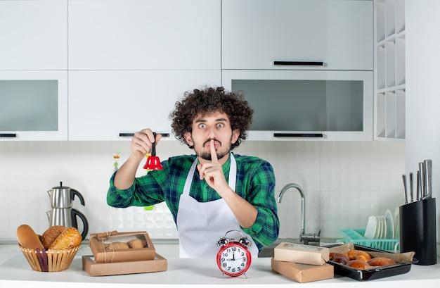 Vista frontal del joven nervioso de pie detrás de la mesa con varios pasteles y sosteniendo una campana de anillo roja haciendo un gesto de silencio en la cocina blanca
