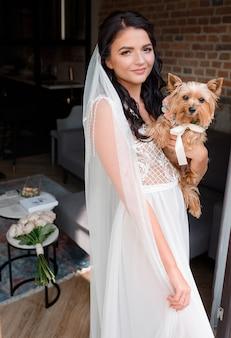 Vista frontal de la joven novia morena sosteniendo un yorkshire terrier en una habitación de hotel