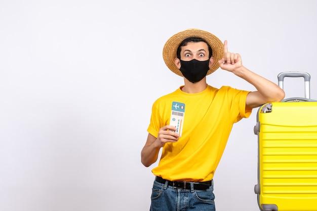 Vista frontal joven de ojos abiertos con sombrero de paja de pie cerca de la maleta amarilla con billete de viaje apuntando con el dedo hacia arriba
