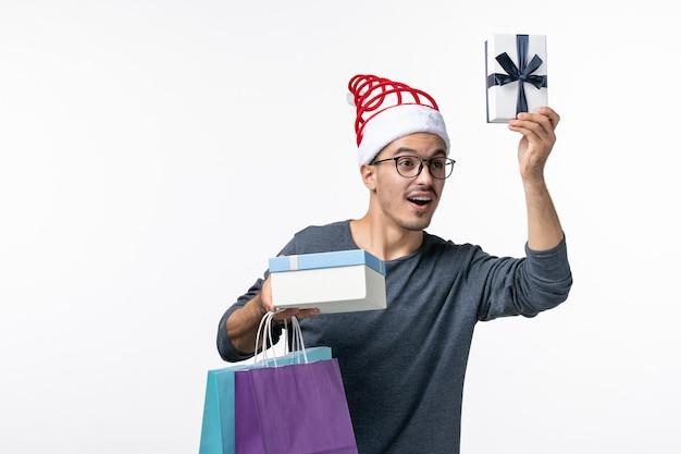 Vista frontal del joven con paquetes y regalos en la pared blanca