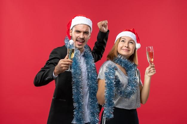 Vista frontal de la joven pareja celebrando el año nuevo en la fiesta de piso rojo amor de navidad