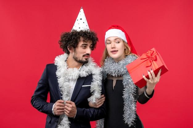 Vista frontal de la joven pareja celebrando el año nuevo en la pared de color rojo claro vacaciones amor de navidad