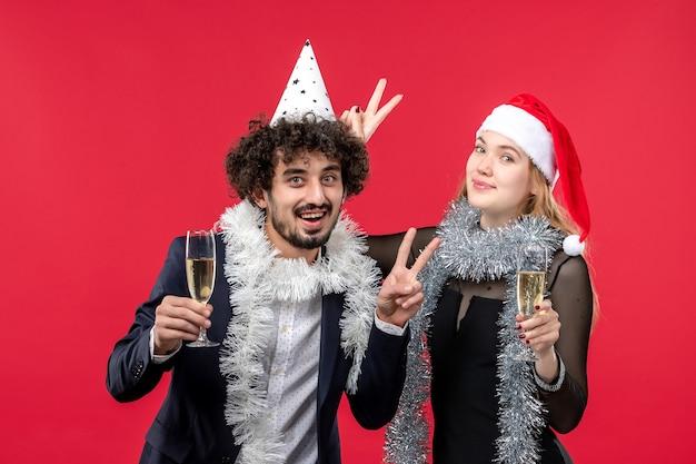 Vista frontal joven pareja celebrando el año nuevo en la pared roja amor fiesta de navidad
