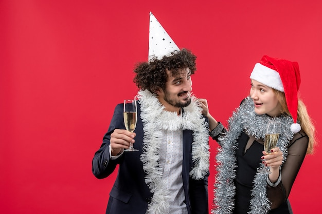 Vista frontal de la joven pareja celebrando el año nuevo en la pared roja fiesta de navidad amor vacaciones
