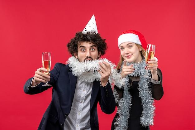 Vista frontal joven pareja celebrando el año nuevo en la pared roja navidad amor vacaciones