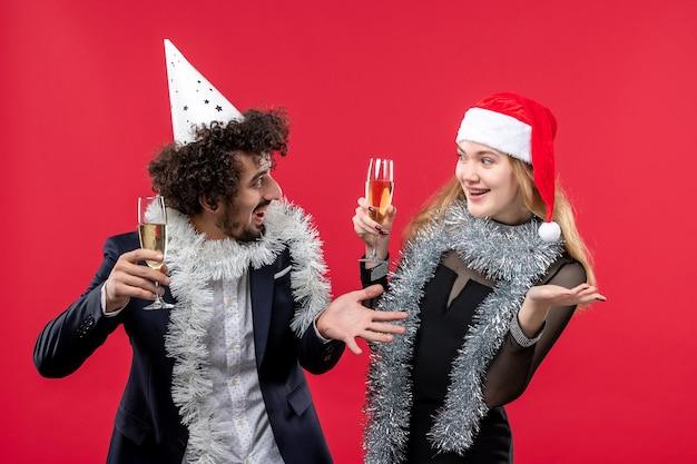 Vista frontal joven pareja celebrando el año nuevo en la pared roja vacaciones amor de navidad