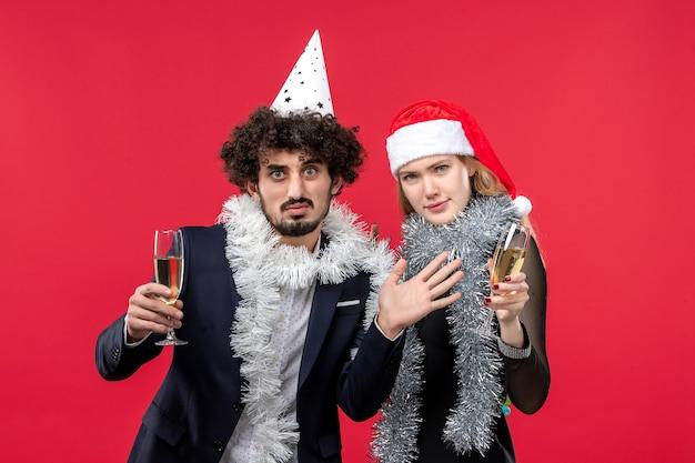 Vista frontal de la joven pareja celebrando el año nuevo en la pared roja vacaciones navidad color amor