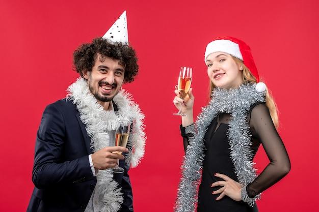 Vista frontal joven pareja feliz celebrando el año nuevo en el amor de navidad de vacaciones de piso rojo