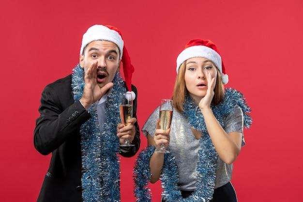 Vista frontal joven pareja feliz celebrando el año nuevo en la pared roja fiesta amor de navidad