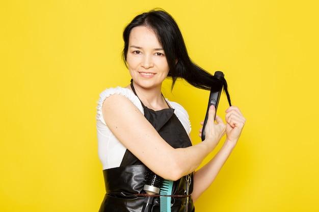 Una vista frontal joven peluquera en camiseta blanca capa negra fijación arreglando su cabello con herramienta sonriendo