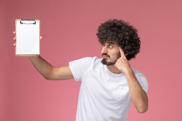 Vista frontal joven pensando mientras mira el cuaderno de oficina blanco