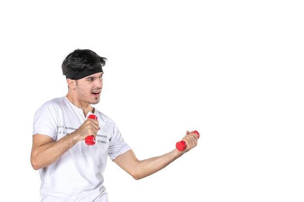 Vista frontal joven con pesas en sus manos luchando contra alguien sobre fondo blanco color cuerpo en forma dieta salud atleta yoga estilo de vida humano deporte