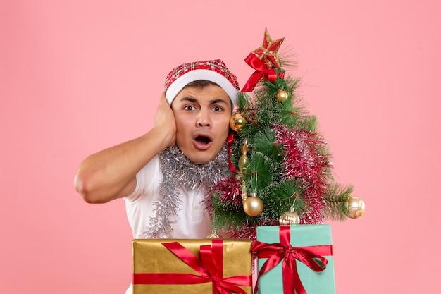 Vista frontal joven de pie alrededor de regalos de navidad sobre fondo rosa