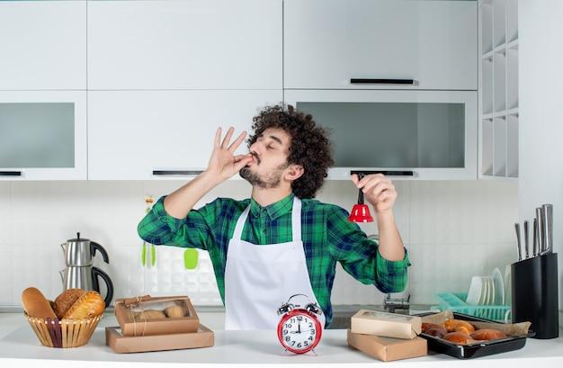 Vista frontal del joven de pie detrás de la mesa varios pasteles en él y mostrando la campana de anillo rojo haciendo gesto de anteojos en la cocina blanca