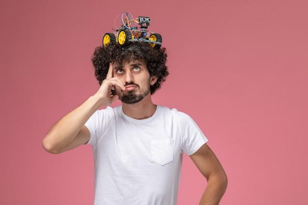 Vista frontal joven poniendo innovación electrónica en su cabeza y pensando