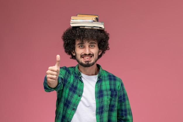 Vista frontal joven poniendo su libro sobre su cabeza y pulgares arriba