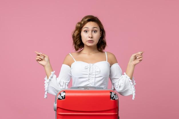 Vista frontal de la joven preparándose para un viaje de verano con bolsa roja en la pared rosa