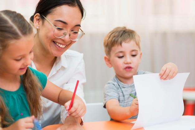 Vista frontal joven profesora ayudando a sus alumnos en clase