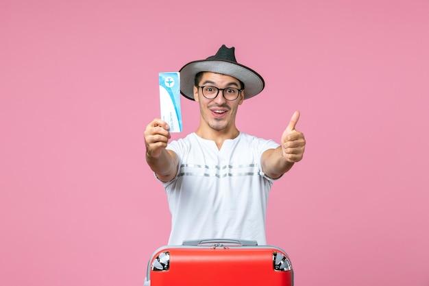 Vista frontal del joven que sostiene el boleto de avión de vacaciones en la pared de color rosa claro