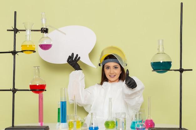 Vista frontal joven químico femenino en traje de protección especial con gran cartel blanco en la pared verde laboratorio químico trabajo de química ciencia femenina