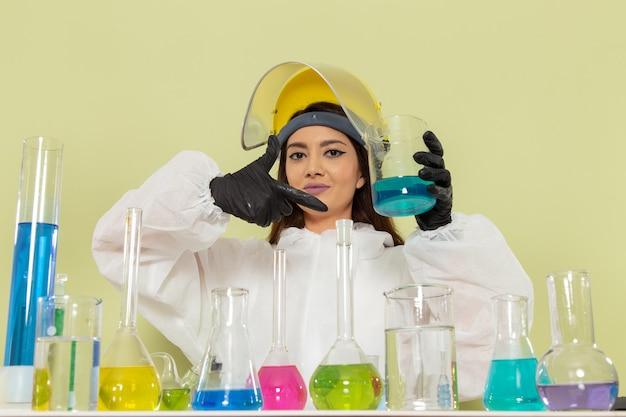 Vista frontal joven químico femenino en traje de protección especial que trabaja con soluciones en la ciencia del trabajo de química de laboratorio químico de pared verde