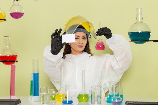 Vista frontal joven químico femenino en traje de protección especial con tarjeta y solución en la pared verde laboratorio químico trabajo de química ciencia femenina