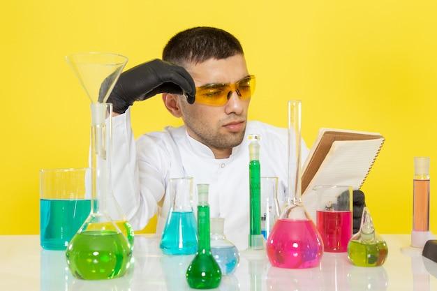 Vista frontal joven químico masculino en traje blanco frente a la mesa con soluciones coloreadas leyendo un bloc de notas en el escritorio amarillo trabajo de ciencia química de laboratorio