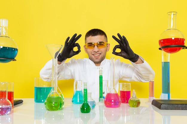 Vista frontal joven químico masculino en traje blanco frente a la mesa con soluciones coloreadas sonriendo y posando en el laboratorio de trabajo de ciencia de escritorio amarillo