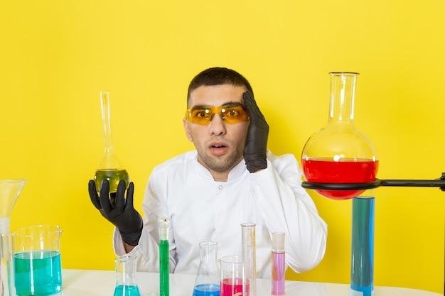 Vista frontal joven químico masculino en traje blanco frente a la mesa con soluciones coloreadas sosteniendo el matraz con cara de sorpresa en el laboratorio de trabajo científico de escritorio amarillo
