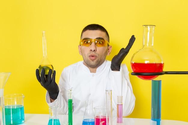 Vista frontal joven químico masculino en traje blanco frente a la mesa con soluciones coloreadas sosteniendo el matraz con expresión de sorpresa en el laboratorio de trabajo científico de escritorio amarillo