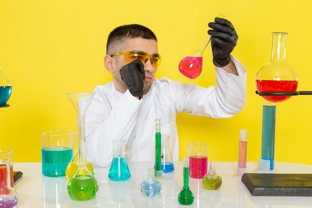 Vista frontal joven químico masculino en traje blanco frente a la mesa con soluciones coloreadas sosteniendo el matraz y pensando en el laboratorio de trabajo científico de escritorio amarillo