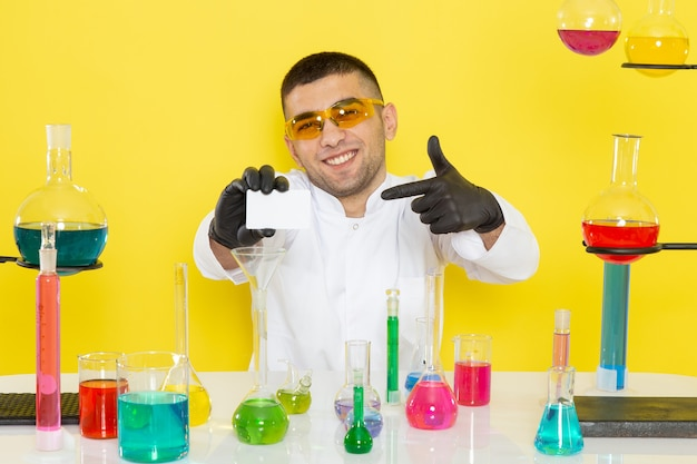 Vista frontal joven químico masculino en traje blanco frente a la mesa con soluciones coloreadas sosteniendo una tarjeta blanca sonriendo en la pared amarilla trabajo de ciencia química de laboratorio