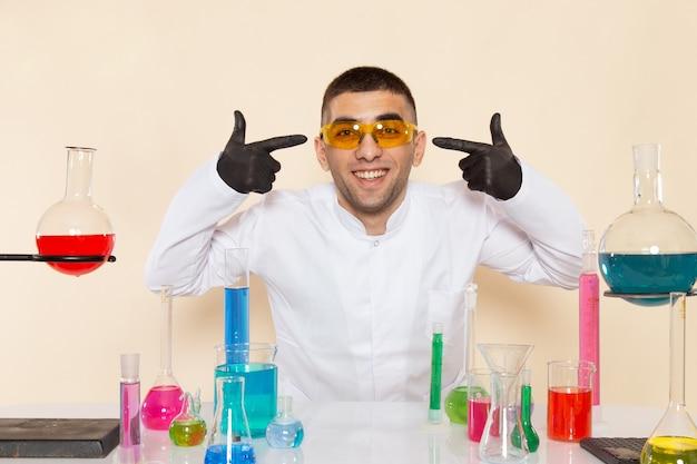 Vista frontal joven químico masculino en traje especial blanco frente a la mesa con soluciones coloreadas sonriendo en la pared crema laboratorio química ciencia trabajo productos químicos