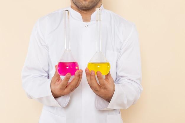 Vista frontal joven químico masculino en traje especial blanco sosteniendo frascos con soluciones amarillas y rosadas en la pared crema química experimento de laboratorio de ciencias