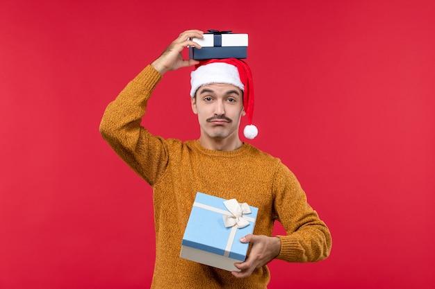 Vista frontal del joven con regalos de año nuevo en la pared roja