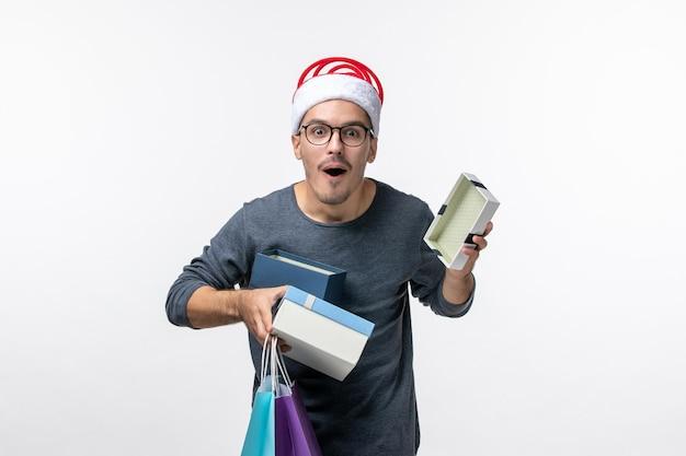 Vista frontal del joven con regalos navideños en la pared blanca