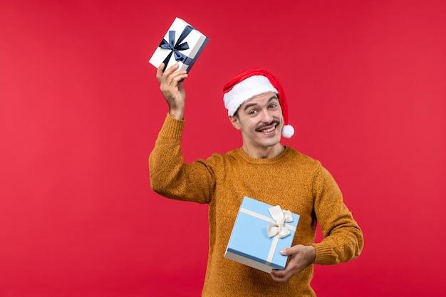 Vista frontal del joven con regalos en la pared roja