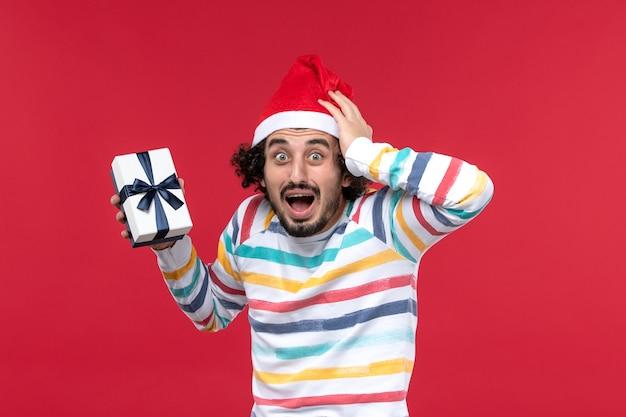 Vista frontal joven con rostro presente y nervioso en la pared roja emoción de vacaciones de año nuevo
