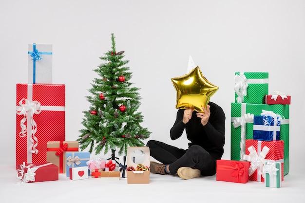 Vista frontal del joven sentado alrededor de regalos y sosteniendo la figura de una estrella dorada en la pared blanca