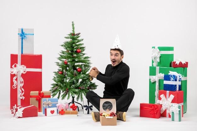 Vista frontal del joven sentado alrededor de regalos de vacaciones decorando arbolito en la pared blanca
