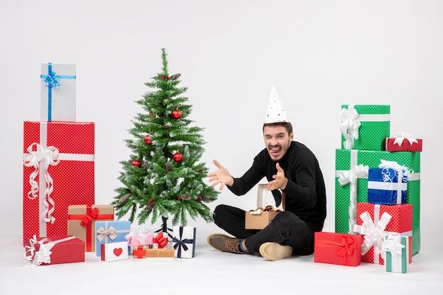 Vista frontal del joven sentado alrededor de regalos de vacaciones en la pared blanca