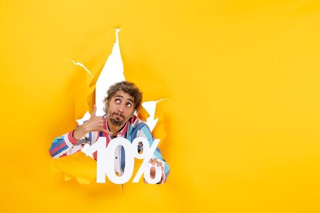Vista frontal del joven serio que muestra el diez por ciento y hace un gesto de llamarme en un agujero rasgado en papel amarillo