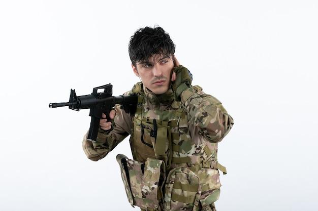 Vista frontal del joven soldado en camuflaje con ametralladora pared blanca