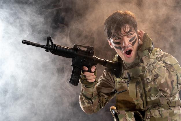 Vista frontal del joven soldado en camuflaje con ametralladora pared negra