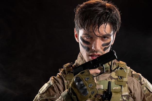 Vista frontal del joven soldado de camuflaje con el objetivo de pistola en la pared negra