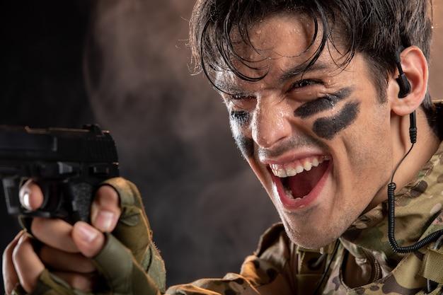 Vista frontal del joven soldado de camuflaje con pistola en pared negra